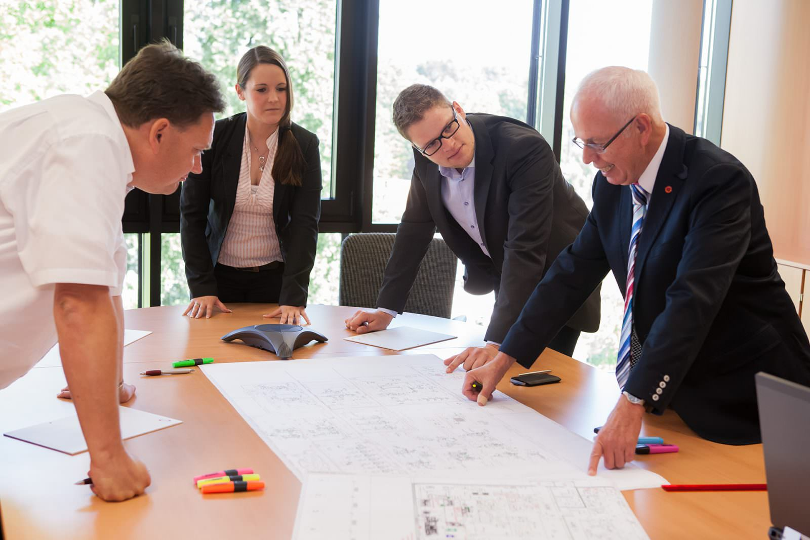 photo of team discussing flow chart and plant desi...