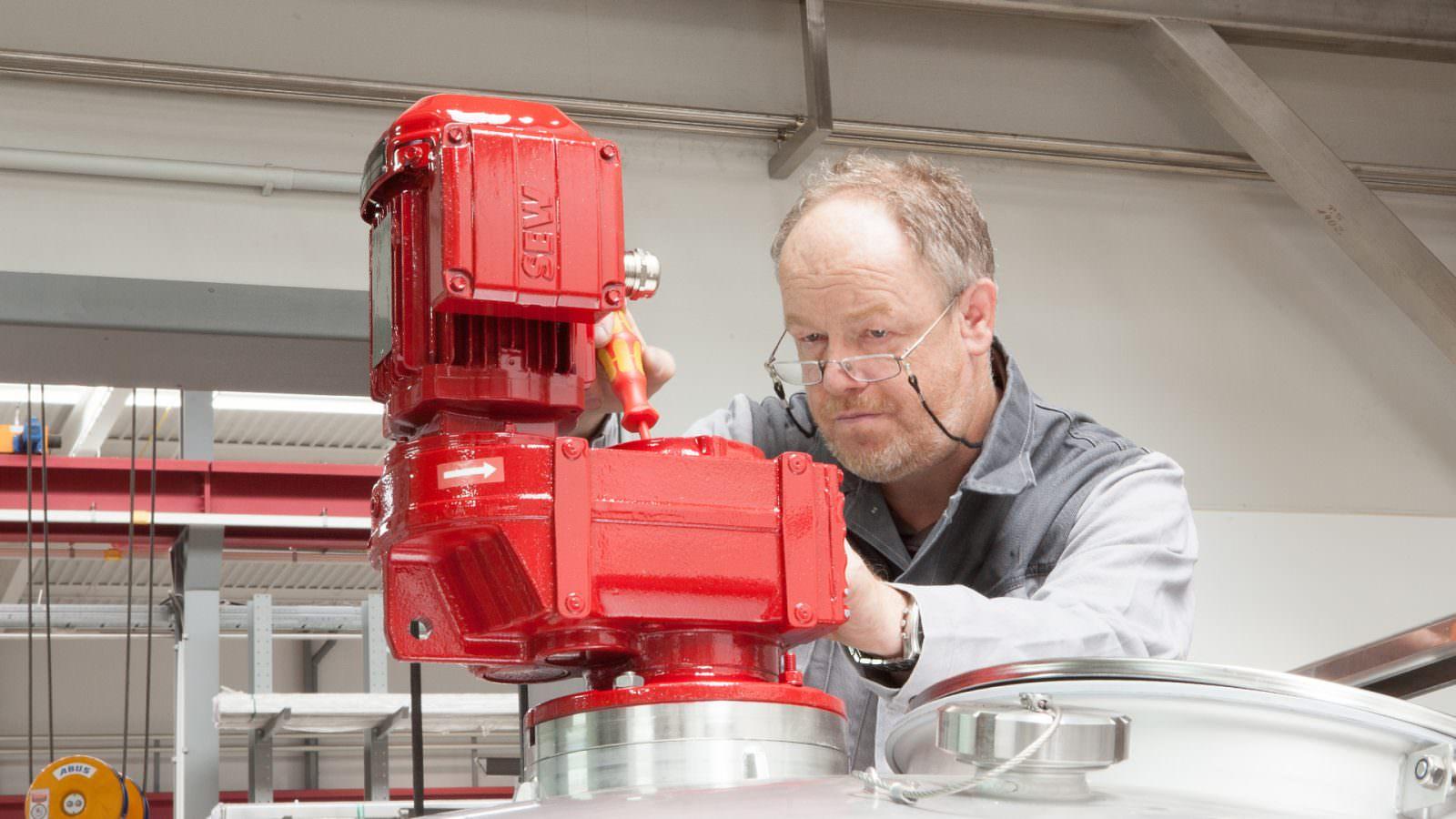 Monteur beim Installieren eines Rührwerks am Behälter