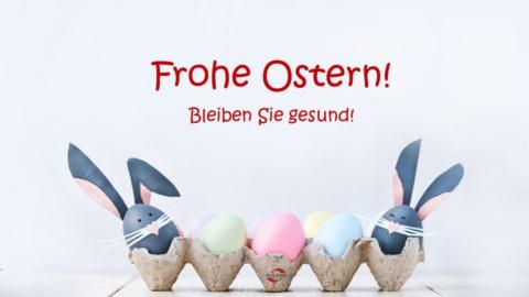 Frohe Ostern, bleiben Sie gesund! Eierkarton mit farbigen Eiern, Osterhasen